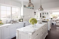 Hamptons-style white kitchen with shaker cabinets, marble splashback, marble benchtops, industrial pendant lamps, timber floorboards