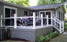 A beautiful Timbertech composite deck with white Radiance railing. Notice the Deckorator pickets accented with Deckorator baskets. Notice how the color of the deck blends perfectly with the home.