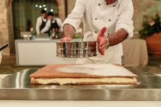 Chef Patrizio placing the powdered sugar on top of the Mille Foglie wedding cake.