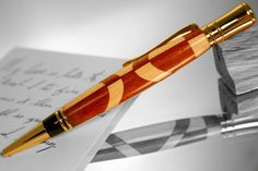 Maple and padauk mirror one another in this elegant handcrafted wood pen with a timeless look. This writing instrument is very comfortable in the hand. It has a subtly curving form, a little shorter than your average pen but slightly more substantial to hold. Its really a joy to use.  The elements of this wooden pen were painstakingly assembled, then drilled, lathed and sanded by hand up to 600 grit. It received a thin coat of teak oil to give the subtle grain some depth. It was then given a…