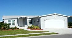 This is a gray manufactured home with white shutters with a double garage in the front of the home Manufactured Homes Floor Plans, Manufactured Homes For Sale, 2 Bedroom Floor Plans, House Floor Plans, Prefab Homes, Modular Homes, Cool Backgrounds For Iphone, Palm Harbor Homes, White Shutters