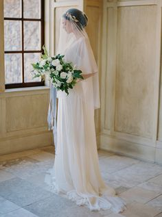 A timeless bride holding her white bouqute in a Sarah Seven gown.