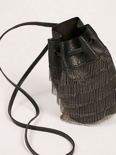 Bardot Fringe Mini Bucket | Mini bucket bag featuring a vegan leather design with glam metal fringe accents throughout. Drawstring style closure.