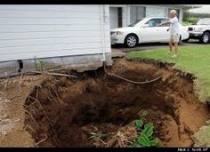 Richard Horita looks at a sinkhole at his home, Wednesday, Oct. 18, 2006, in Paauilo that was caused when a 6.7 earthquake struck the island of Hawaii. (Mark J. Terrill, AP)