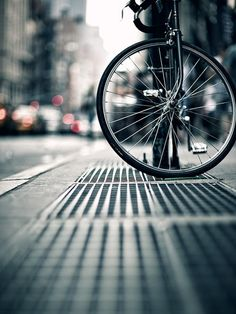 Bike wheel on a city street.  Amazing creativity and composition!