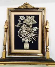 This framed art is made from antique and vintage quality rhinestone jewelry including a shoe clip, earrings, and brooches. The antique frame is beautiful work of art on its own. As with anything hand-made and vintage, there may be small irregularities in workmanship and/or