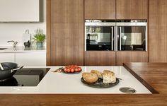 Modern walnut and white kitchen in Wimbledon featuring: split level island, integrated appliances, breakfast cupboard & sleek handle-less kitchen storage.