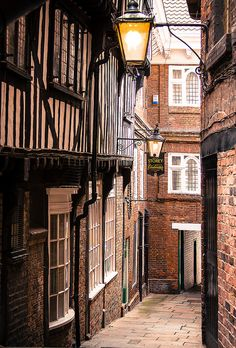 A narrow, old street in York, England, UK. Some streets are so narrow , two people could touch hands by reaching out of the upstairs windows.