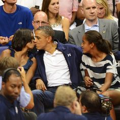 President Barack Obama kisses first lady Michelle Obama as daughter Malia ® looks on, while they attend the Olympic men's exhibition basketball game between Team USA and Brazil in Washington July. Barack Obama Birthday, Barack Obama Family, Malia Obama, Obama President, Obamas Family, Black Presidents, Greatest Presidents, American Presidents, American History