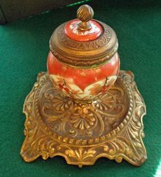 This unusual and beautiful inkwell dates to the 19th Century. It is made of porcelain in the Kutani style, which is from Japan. It is trimmed and set on a gilt bronze base that appears to be French in origin. It was common in the mid to late 19th Century to import porcelain from the Orient and then fashion it into objects appealing to Westerners.