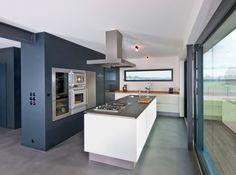 Moderne Küche mit bodentiefen Fenstern und Kochinsel im Bau-Fritz Holzhaus