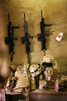 Royal Marine SA80 rifles hang on a wall above Medical Section kit ready to be grabbed in the event of an emergency, at Forward Operating Base Gibraltar in the Gereshk Valley Afghanistan.