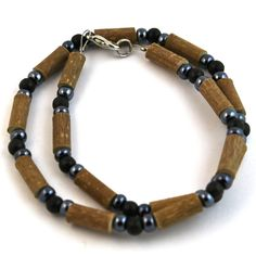 Hazelwood Black & Hematite Necklace! Effective in reducing acid-based ailments and symptoms, such as eczema, acid-reflux, and heartburn, and ulcers. Must be placed directly on the skin and worn 24/7. Made with nylon-coated steel wire, hazelwood and assorted beads, and nickel clasp (lobster style opening).