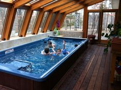 The 15' Endless Pools® Swim Spa turns this sunroom into a family fun center - perfect for a gray winter's day. For more ideas, visit http://www.endlesspools.com/tour-sunroom-pools.php.