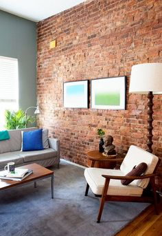 Midcentury modern living room in soothing colors and exposed brick wall
