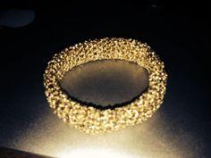 Een gehaakte armband met goudkleurige draad.