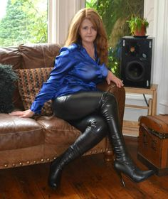 Blue satin blouse, leather pants, leather high heel boots.