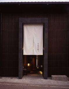 古い町並みに似合うファサードのなかに設けられた入り口。白い暖簾と焼杉の小割が印象的(写真:淺川 敏)
