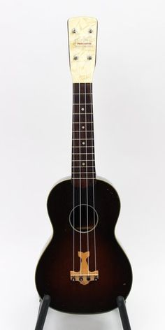 """This is a mid-sized uke made of curly mahogany. The pearloid peghead overlay reads """"Johnny Marvin Professional Tenor Ukulele"""" but is more like a concert in size. The body measures 10-3/4"""" in length with a 14-7/8"""" scale length. The nut width is a confortable 1-1/2"""" wide. The airplane shaped pin bridge commemorates the famous Lindbergh transatlantic flight. The instrument comes in the original purple lined hard shell case."""