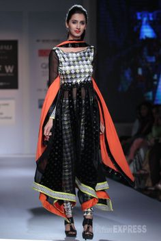 A model displays a black and white churridar suit with a hint of neon orange and green by designer Archana Kochar. #Fashion #Style #Beauty