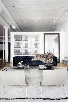 Modern loft living room. Blue sofa, white walls, beni ourain rug.