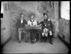 Three unidentified men in costumes, dressed as a German, a sailor and a Scotsman with kilt, with table, food and drink and painted outdoors backdrop within a small room, probably Christchurch region