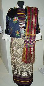 The woman's kera is an ankle length dress. Made from finely woven fabrics, the kira has traditional and beautifully coloured patterns. Under the kera, woman wear a wonju (blouse) which is held in place over the shoulder with a koma (silver buckle). Decorations, colours and texture determine the woman's social status and class. Usually over the dress a toego (open jacket) is worn. The outfit is completed by necklaces made from turquoise, corals, pearls, agateRevo Tours & Adventure Bhutanese…