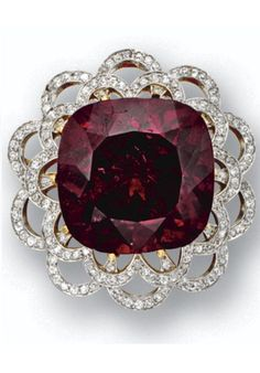 Spinel and diamond pendant-brooch, Tiffany & Co., circa 1900. The cushion-shaped red spinel weighing 48.52 carats, within a lacework frame of scalloped outline set with small round diamonds, mounted in gold and platinum, signed Tiffany & Co.