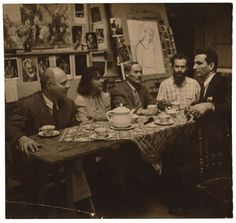 Carl Holty (left) and Joan Miró (center), with others at a tea party in an artist's studio, 1947
