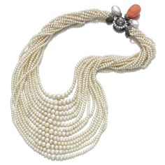 PEARL, CORAL AND DIAMOND NECKLACE, MONTURE CARTIER, 1930S Composed of thirteen rows of graduated pearls measuring approximately from 2.7 to 6.9mm, the clasp highlighted with a grey pearl bordered by circular-cut diamonds together with two pearls and one coral drop capped by rose-cut diamonds.
