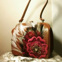 OOAK Repurposed Vintage Handbag A UNIQUE GIFT FOR VINTAGE LOVERS!!! This is a tan/brown leather, vintage Simco handbag. I repurposed this with a variety of feathers, a vintage lace flower, and a removeable copper metal vintage floral broach. This is ONE OF A KIND and is quality made!! Vintage wear to goldtone metal for that antiqued vintage look. Outside of bag is in great vintage condition, inside is in good vintage condition (100% usable, but some rough edges and signs of general use over…