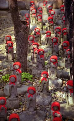 "Jizo statues in Kamakura, Japan. Jizo take care of the souls of unborn children and those who died at a young age. Children ""in limbo"" in Japan are said to go to a place called sai no kawara, where they must create piles of stones into small towers. But every night the stone towers are destroyed by demons, so the next day the children must make new piles of stones. The making of these towers is to help their parents accrue merit for their own afterlife."