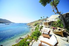 View of the sea from sun chairs in garden area above the Kivotos Hotel's private beach in Mykonos