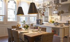 deulonder.com  ~Stunning dining area in kitchen with rectangular dining table, wolven dining chairs, black cone pendant lights, creamy white, kitchen cabinets & kitchen island, stainless steel pot rack, pot filler, subway tiles backsplash and charcoal gray walls paint color.
