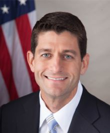 A portrait shot of Paul Ryan, looking straight ahead. He has short brown hair, and is wearing a dark navy blazer with a red and blue striped tie over a light blue collared shirt. In the background is the American flag.