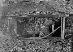 Two miners working at the coalface in Ashington Colliery. One tends the coal cutter, whilst the other follows clearing the cuttings