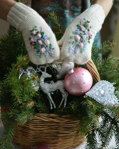 very pretty embroidered gloves holding a basket of assorted christmas decorations