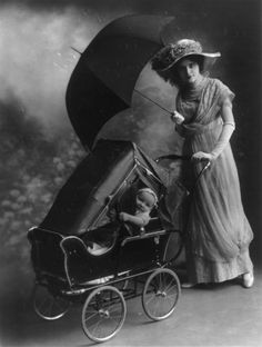 Woman with a baby stroller and an umbrella, 1913 Love vintage photos!