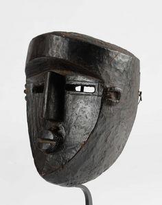 Très beau masque Lwalwa, République Démocratique du Congo Masque représentant un visage humain stylisé aux formes géométriques. La surface du crâne ornée de motifs géométriques. Bois incrusté d'une profonde patine sombre. Haut : 27 cm. Larg : 17 cm