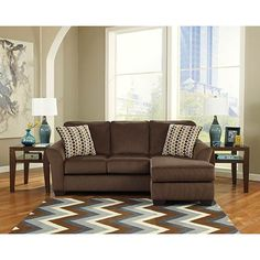 Bring an artistic contemporary design to your living room with the adjustable Ashley 'Geordie-Cafe' Sofa Chaise. With flared arms and supportive seat cushions wrapped in soft upholstery fabric, this sofa is both fashionable and comfortable. Because the chaise can be moved to either side of the sofa, it's easy to fit this piece in any home.