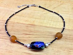 Beautiful large painted recycled glass bead with coordinating recycled translucent beads, both crafted in Ghana, and strung with seed beads and metal beads from Ethiopia. Necklace measures 7-inches with adjustable chain.