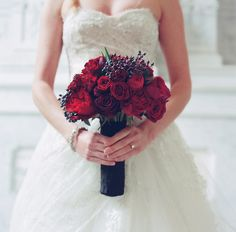 I couldn't find the source for this image.  Love the deep reds in the bouquet, and the fabric on the dress.
