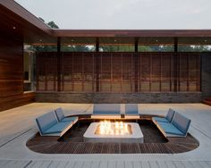 Sunken fire pit with custom ipe screen fence at the Curved House