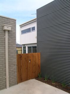 Design palette of face brickwork, Colorbond steel, stained cyprus slats and painted Matrix cladding used throughout three unit residential development at North Shore.