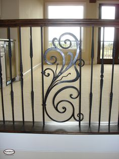 mixing wood with iron balustrades | wrought iron panels used as a centerpiece