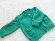 This sweet little cardi comes in sizes from birth through to 7 years. A traditional cardigan with a little bit of cable work on the sleeves and pockets, just enough detail to keep you interested whilst knitting. Charts for the sleeve cables and the pockets are included, also written out for those who do not like to work with charts. Worked in one piece to underarm.