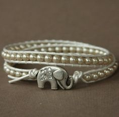 MORE THAN JUST A WRAP BRACELET!!!.... An elephant with it's trunk raised up is considered to bring good luck and an excellent fortune and to have the magical power to take away troubles. Metallic cream leather with taupe freshwater pearls and antique silver elephant button adorned with Swarovski crystal rhinestones. To make a purchase please go to my online store www.theluckyelephant.etsy.com.