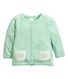Fine-knit cardigan in soft cotton. Buttons at front and narrow ribbing at neckline, cuffs, and hem.