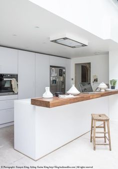 Overall white, steel appliances and blond oak bar top, modern simplicity