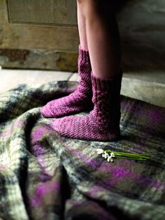 ~Heather of the Moors~Rowan.  Sock toes are in focus, color matches blanket.  Flowers for romance.  Staging does not need to be elaborate. Contrast:  texture and light. How the eye is lead: lines created in the blanket, the vertical line created by the legs, position of feet, and the strong shadow along the instep of the far foot. Light source: almost spotlight on toes.  Highlights the pattern. Simplicity, feminine, sensual, innocence.  Romance does not have to be complicated.